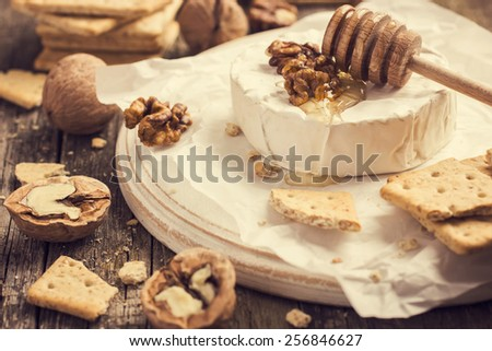 camembert cheese with crackers, nuts and honey, toned - stock photo