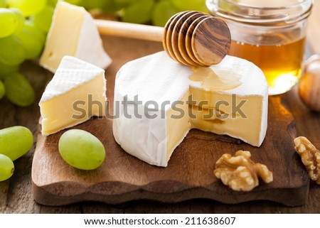 camembert cheese with grapes, honey and nuts on wooden background - stock photo
