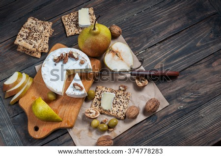 Camembert cheese with walnuts, honey and pears on rustic table. Glass of white wine. Top view. - stock photo