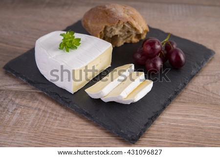 Camembert with bread and red grapes - stock photo