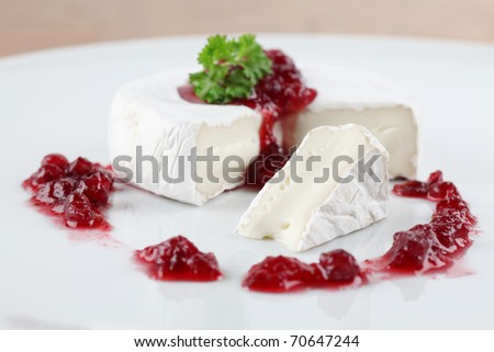Camembert with cranberry jam and parsley on white plate. Shallow dof - stock photo
