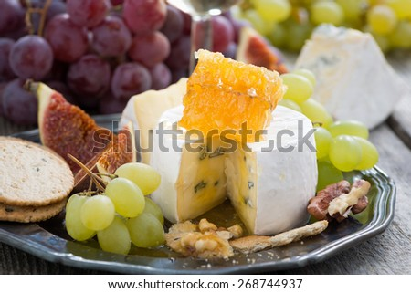 camembert with honey and fruit, snack on a plate, close-up - stock photo