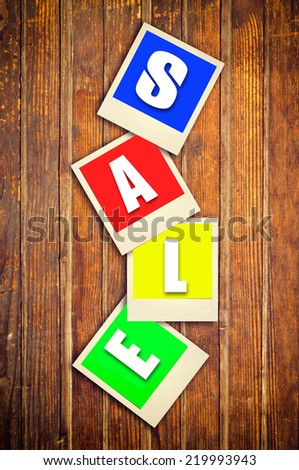 Camera film with sale letters on photos attached with tape on wooden background - stock photo
