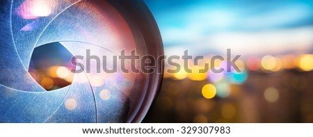 Camera lens on blur nigth city  - stock photo