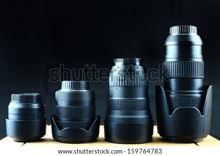 Camera lenses in various sizes on dark backdrop background. - stock photo