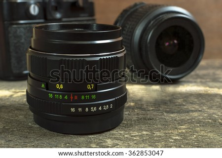Camera lenses on wooden table. Selective focus. - stock photo