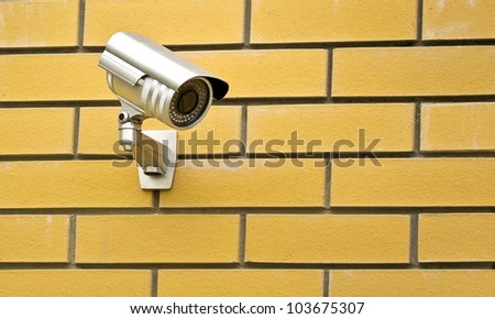 camera on a brick wall of the house - stock photo