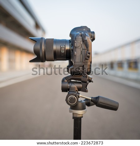 Camera on tripod isolated shot outdoors. - stock photo