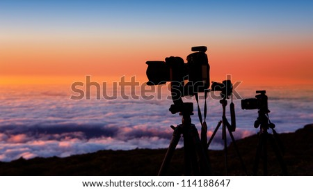 camera tripods of nature photographer work in high mountain sunset over sea of clouds - stock photo