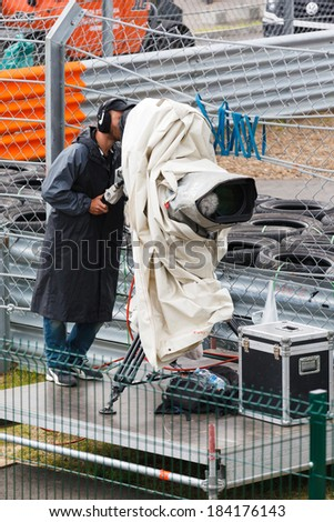 cameraman filming a sporting event on a stadium in the rain - stock photo