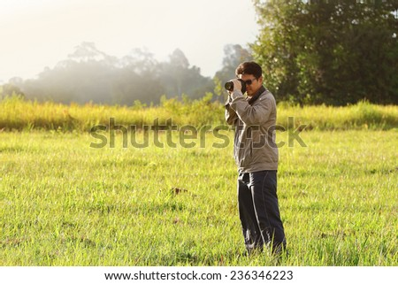 cameraman shooting camera in natural sunshine - stock photo