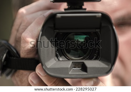 Cameraman shooting with a professional camera - stock photo