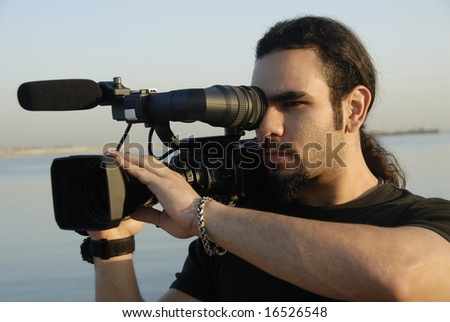 CameramanA Professional Cameraman Filming Footage On Location - stock photo
