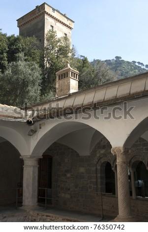 Camogli, San Fruttuoso Abbey cloister - Portofino Natural Park The Monastery Complex and Doria tower behind - Protected Marine Area of Portofino Natural Park - Ligurian Riviera - Liguria Italy - stock photo