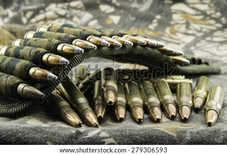 camouflage ammunition belt for rifle  on camouflage background - stock photo