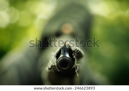 Camouflage hunter aiming with his rifle  - stock photo