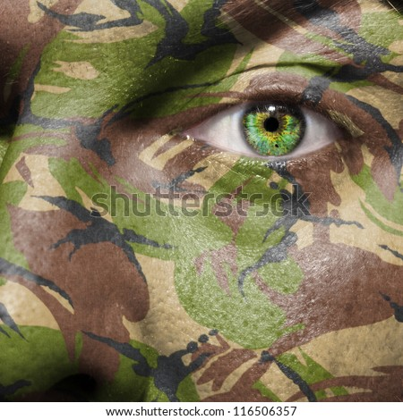 Camouflage painted on a face with green eye to portray military personnel or guerrilla - stock photo