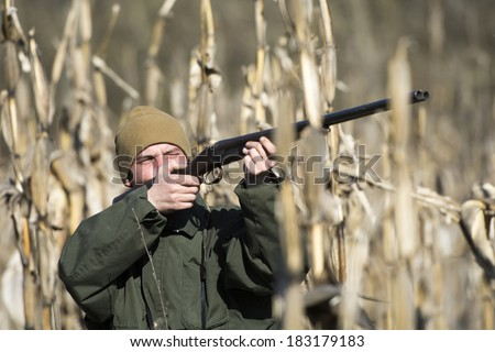 Camouflaged hunter hunting patridges in field  - stock photo