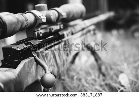 Camouflaged sniper rifle with spotting scope and equipment. Photo edited into warfare black and white look and dark atmosphere. Selective focus. - stock photo