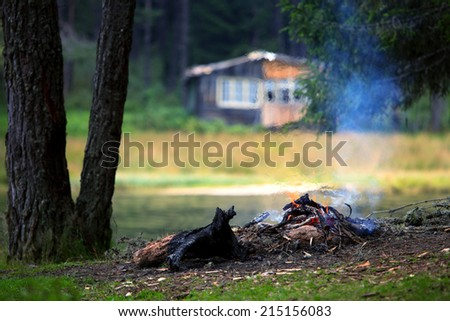 camp fire near lake in autumn time with wooden villa in background  - stock photo
