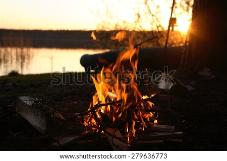 Camp-fire on river bank an sunset - stock photo