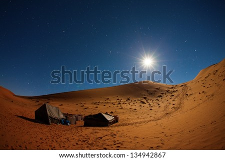 Camp in Sahara Desert in night with moon as star and moving stars - stock photo