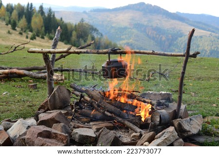 Camp kettle is heated on a fire  - stock photo