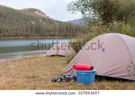 Camp of two tents pitched up on shore of Yukon River in remote wilderness of Yukon Territory, Canada - stock photo