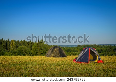 camp tents on the meadow - stock photo
