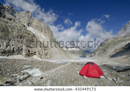 Camp with a red tent on the Leschaux glacier in the french Alps - stock photo