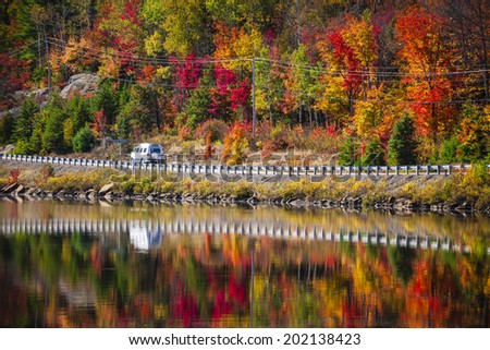 Camper driving though fall forest with colorful autumn leaves reflecting in lake. Highway 60 at Lake of Two Rivers, Algonquin Park, Ontario, Canada. - stock photo
