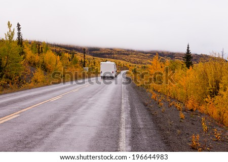 Camper van drives on highway with autumn or fall colorful yellow foliage of boreal forest taiga of yukon Territory, Canada - stock photo