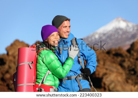 Campers couple hiking enjoying looking at view embracing in love. Romantic hiker man and woman wearing backpacks enjoying sunset during hike on mountain volcano Teide, Tenerife, Canary Islands, Spain. - stock photo