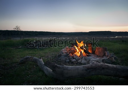 Campfire at dusk with woodpile and lake in background - stock photo