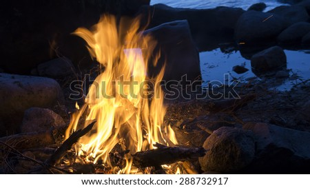 Campfire burning on the beach of a lake at night with water in the background. - stock photo