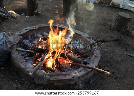 Campfire in fire pit at campsite. - stock photo