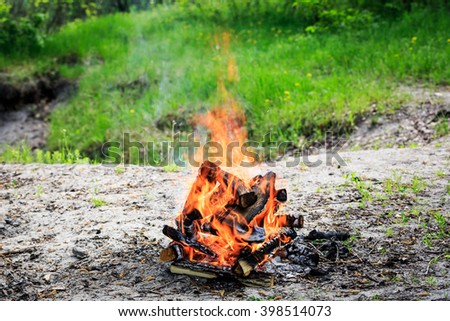 campfire on meadow in forest - stock photo