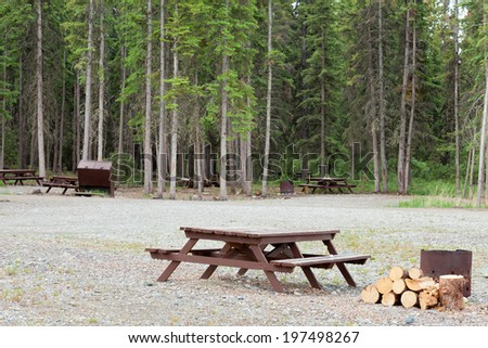 Campground on gravelled area inforest with camping table and fire-pit for each campsite - stock photo