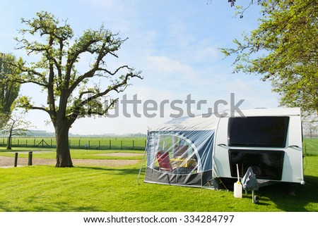 Campground with caravan in spring - stock photo
