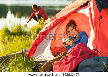 Camping girl sitting in tent drinking from pot - stock photo