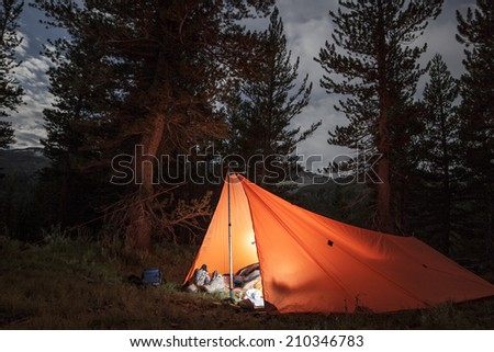 Camping in a lit up tent/tarp in the wilderness in Yosemite National Park - stock photo