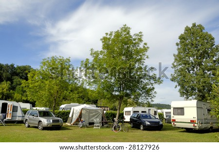 Camping in France with caravans between trees - stock photo