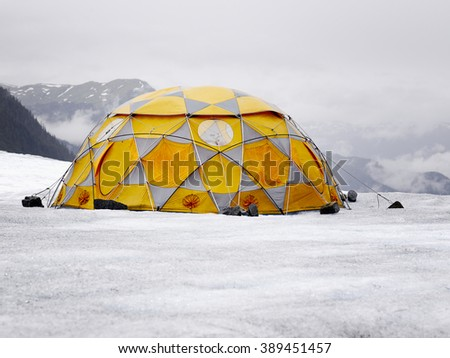 Camping in the high mountains. Orange and grey tent on the glacier. - stock photo