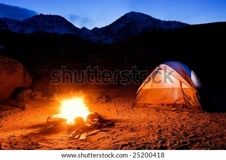 Camping In The Mountains, Camp Fire and Tent at Sunset - stock photo