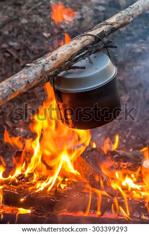 Camping kettle on the fire at an outdoor campsite Kettle for coffee while camping - stock photo