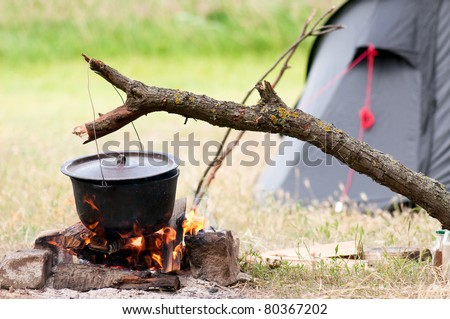 Camping kitchenware - pot on the fire at an outdoor campsite - stock photo