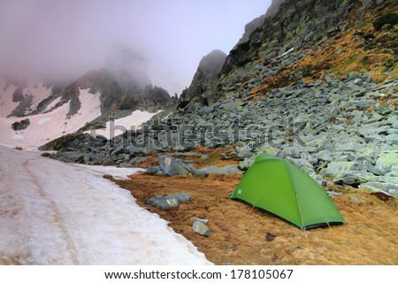 Camping site and green tent on the mountain in cloudy weather - stock photo