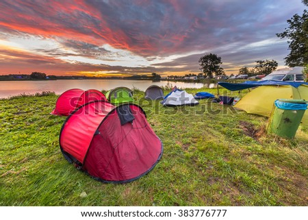 Camping spot with dome tents near lake on a music festival camp site under beautiful sunrise - stock photo