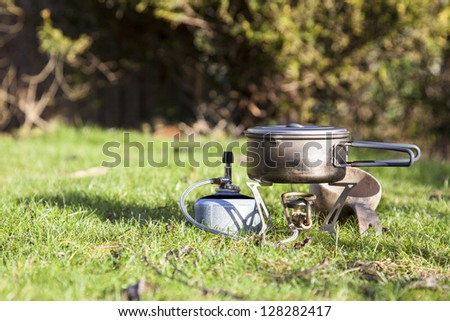 Camping stove with titanium pot and wooden cup - stock photo
