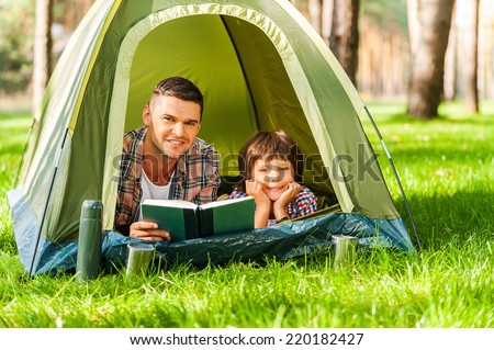 Camping together is fun. Father and son reading book and smiling while lying in tent together - stock photo